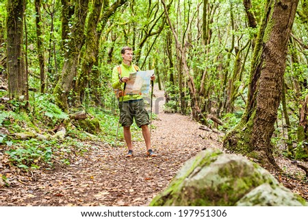 Man hiker hiking in green forest. Young male looking at map and planning trip or get lost in green beautiful magical forest, La Gomera, Canary Islands. - stock photo