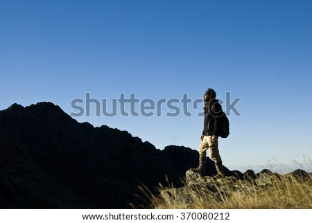 Man hiker on a top of a mountain  - stock photo