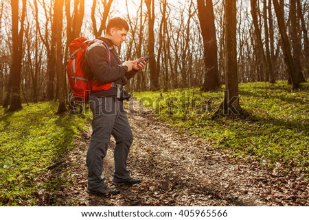 Man hiker taking photo with smart phone in forest - stock photo