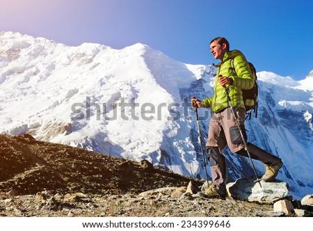 Man hiker trekking exploring in high Himalaya Mountains in Nepal - stock photo