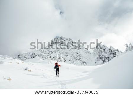 Man Hikes Through Snow Toward Peak - stock photo
