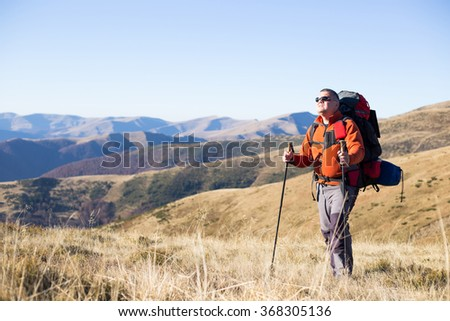 Man hiking in the mountains with a backpack and tent. - stock photo