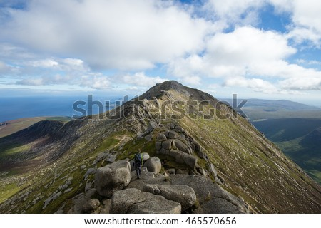 Man hiking on huge mountain peak in Scotland. View of Scottish Highlands on Isle of Arran.
