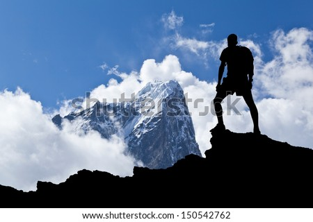 Man hiking silhouette in Himalaya mountains. Male hiker with backpack on top of mountain looking at beautiful morning at Taboche in Himalayas, Nepal - stock photo