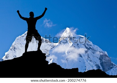 Man hiking success accomplish silhouette in mountains. Male hiker with arms outstretched on top of mountain looking at beautiful Himalayan landscape. - stock photo