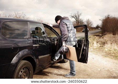 Man hitch-hiking on local European route boarding - stock photo