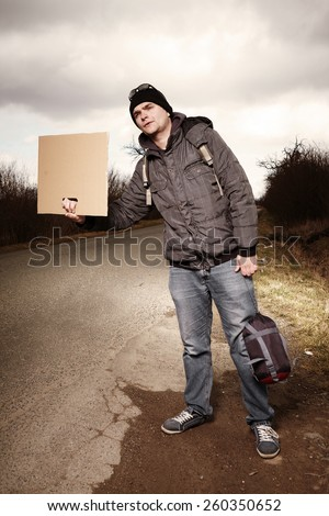 Man hitch-hiking on route with blank cardboard - stock photo