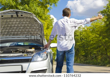 Man hitchhiking by a broken car - stock photo