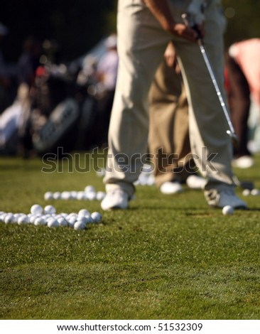 Man hits range balls at the practice area - stock photo