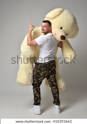 Man hold big teddy bear soft toy as a present to his girlfriend for birthday party on grey background - stock photo