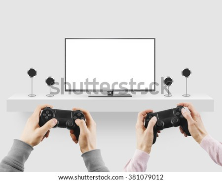 Man hold gamepad in hands in front of blank tv screen mock up playing game. Clear monitor mockup with gamer first person. Men play video games on console station. People gaming contest. Two players. - stock photo