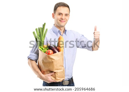 Man holding a bag of groceries and giving thumb up isolated on white background - stock photo