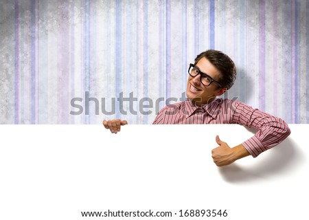 man holding a banner in front of him, his thumb up, smiling - stock photo