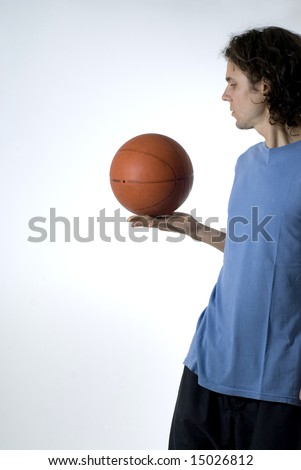 Man holding a basketball and balancing it as he stares at it. Vertically framed photograph
