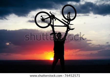 Man holding a bicycle over himself on sunset background - stock photo