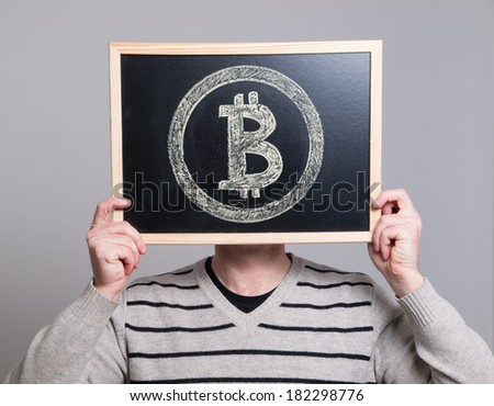 man holding a blackboard with bitcoin symbol isolated on grey background. - stock photo