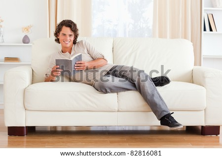 Man holding a book in his living room - stock photo