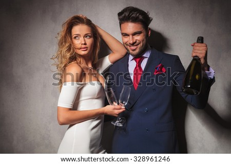 man holding a bottle of champagne saying cheers with his woman next to him. hot fashion couple ready to celebrate - stock photo