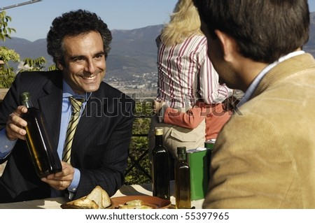 Man holding a bottle of olive oil - stock photo