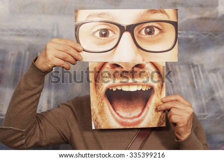 man holding a card with a big smile and big glasses on it - stock photo
