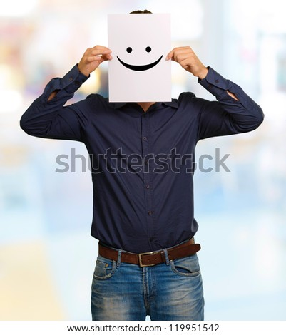 Man holding a card with face paper, outdoor - stock photo
