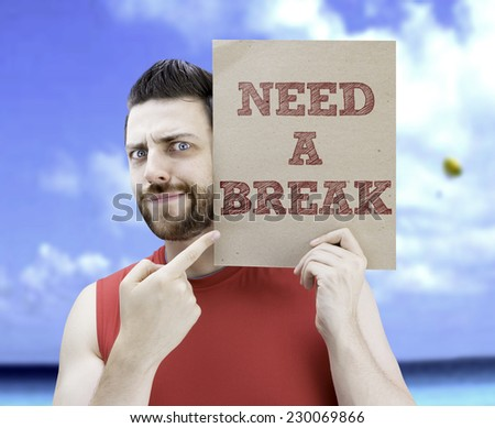 Man holding a card with the text Need a Break on a beach background - stock photo