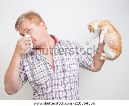 Man holding a cat is allergic to animals - stock photo