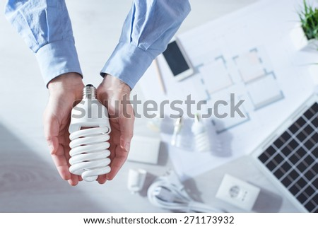 Man holding a CFL energy saving lamp, solar panel and house project on background, top view - stock photo