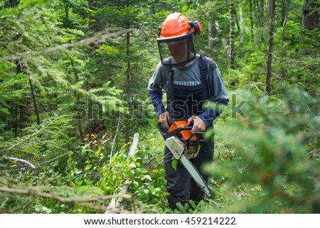 Man holding a chainsaw and wearing a safety helmet in the woods.