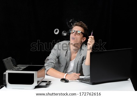 man holding a cigar while using a laptop - stock photo