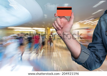 Man holding a credit card in his hand at shopping mall  - stock photo