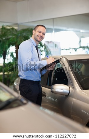 Man holding a file in a dealership