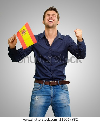 Man holding a flag and cheering on grey background - stock photo