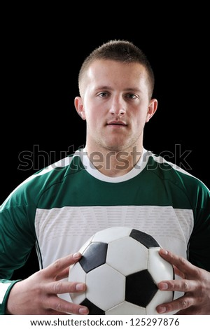 Man holding a football over black background - stock photo