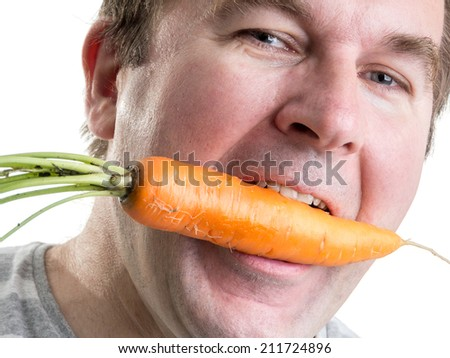 Man holding a fresh carrot in his mouth - stock photo