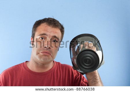 Man holding a gas mask while looks it with sad face - stock photo
