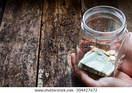 man holding a glass jar for donations - stock photo