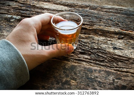 man holding a glass of alcohol - stock photo