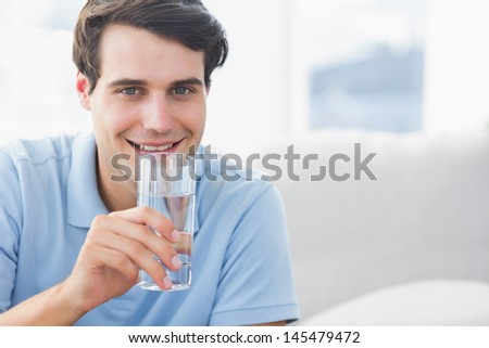 Man holding a glass of water while he is sat on the couch - stock photo