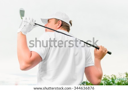 man holding a golf club behind his back