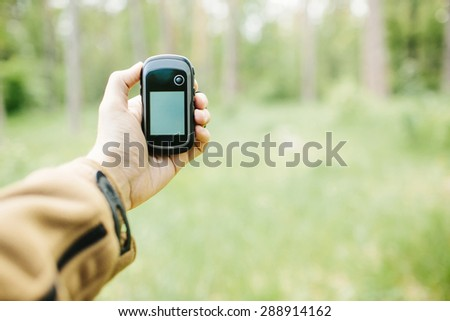 Man holding a GPS receiver and plan in his hand. Handheld GPS devices are used predominantly in the outdoor leisure industry for walking and hiking. - stock photo
