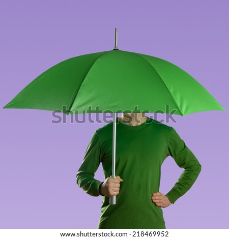 Man holding a green umbrella against a violet background - stock photo