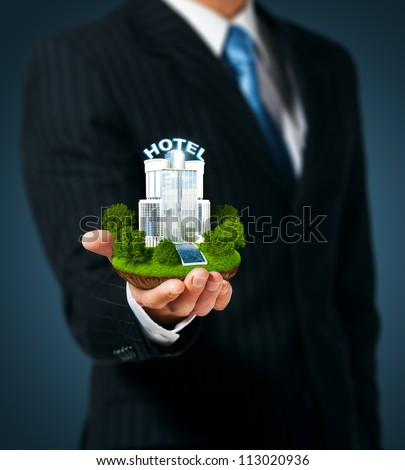 Man holding a hotel in hand - stock photo