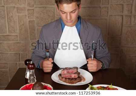man holding a knife and a fork ready to eat a beef steak