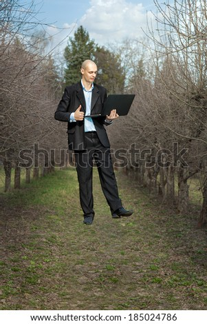 man holding a laptop and levitates. - stock photo