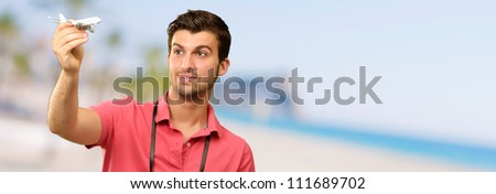 Man Holding A Miniature Of An Airplane, Outdoor - stock photo