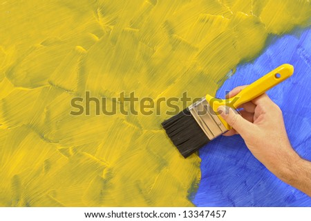 Man holding a paintbrush with a partly finished blank blue and yellow painted wall.  Space for copy. - stock photo