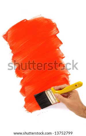 Man holding a paintbrush with a partly finished blank red and white painted wall.  Space for copy. - stock photo