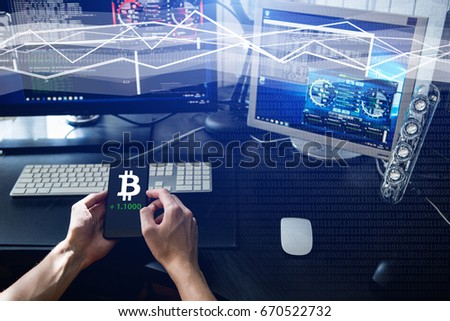 Man holding a phone with a bitcoin exchange rate.