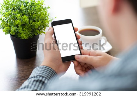 man holding a phone with isolated screen at a table in a cafe
